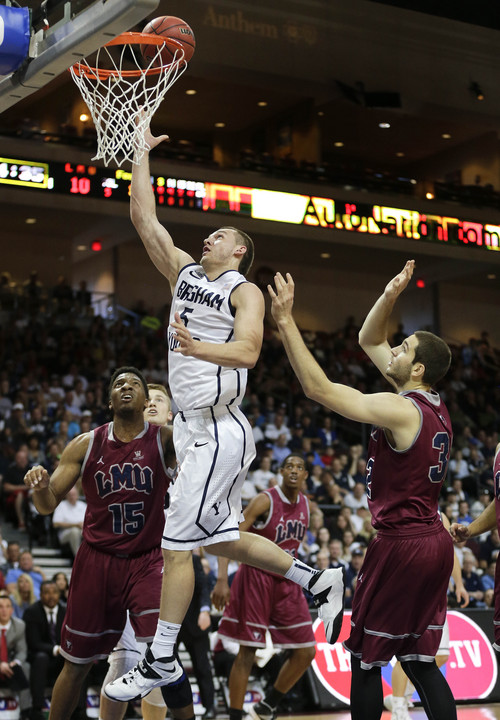 BYU's Kyle Collinsworth (5) shoots against Loyola Marymount's Alex Osborne (15) and Gabe Levin (32) in the first half of a quarterfinal West Coast Conference NCAA college basketball tournament game on Saturday, March 8, 2014, in Las Vegas. (AP Photo/Julie Jacobson)