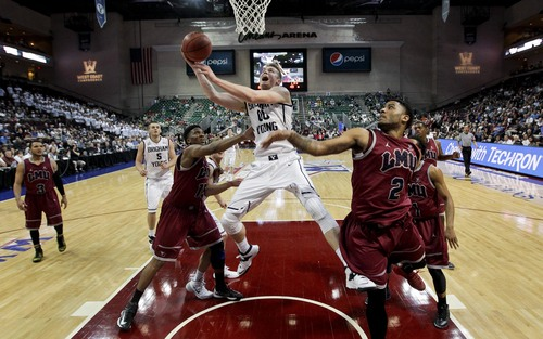 BYU's Eric Mika (00) shoots against Loyola Marymount's Alex Osborne, left, and C.J. Blackwell (2) in the second half of a quarterfinal West Coast Conference NCAA college basketball tournament game on Saturday, March 8, 2014, in Las Vegas. BYU won 85-74. (AP Photo/Julie Jacobson)