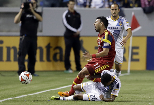 Real Salt Lake midfielder Javier Morales (11) and Los Angeles Galaxy defender James Riley (26) tangle in the first half of an MLS soccer game in Carson, Calif., Saturday, March 8, 2014.  (AP Photo/Reed Saxon)