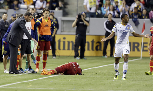 Real Salt Lake midfielder Javier Morales (11) lies on the field near head coach Jeff Cassar gestures, left, as Los Angeles Galaxy defender James Riley gestures at right in the first half of an MLS soccer game in Carson, Calif., Saturday, March 8, 2014.  Real Salt Lake won, 1-0.  (AP Photo/Reed Saxon)