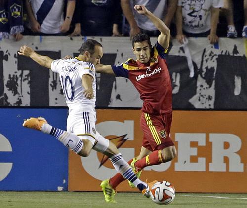 Real Salt Lake defender Tony Beltran covers as Los Angeles Galaxy midfielder Landon Donovan attacks in the first half of an MLS soccer game in Carson, Calif., Saturday, March 8, 2014.  Real Salt Lake won, 1-0. (AP Photo/Reed Saxon)