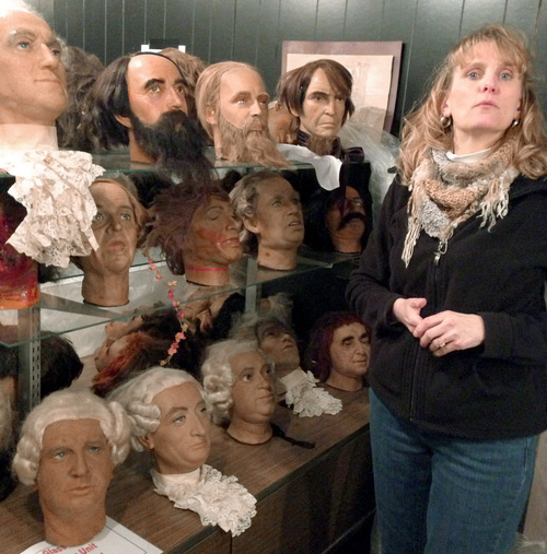 In this photo made on Thursday, March 6, 2014, Tammy Myers, who runs the American Civil War Wax Museum for FutureStake Inc., stands beside shelves of heads of characters from the museum in Gettysburg, Pa. The museum, which has occupied a prime spot near the center of the Gettysburg battlefield for over 50 years, is undergoing an extensive renovation and a new approach to history, so it is selling dozens of its historical figures, most made of vinyl, not wax, in a March 15, 2014 auction. (AP Photo/stf-Mark Scolforo)