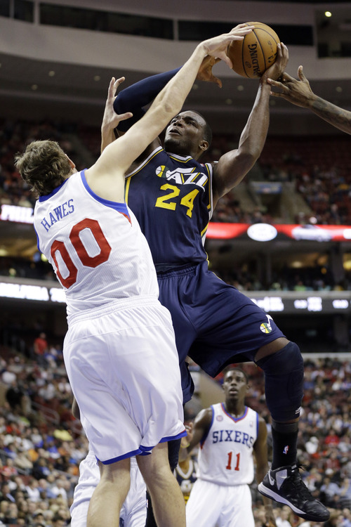 Utah Jazz's Paul Millsap (24) tries to get a shot past Philadelphia 76ers' Spencer Hawes (00) in the second half of an NBA basketball game, Friday, Nov. 16, 2012, in Philadelphia. Philadelphia won 99-93. (AP Photo/Matt Slocum)