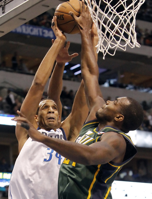 Dallas Mavericks' forward Brandan Wright (34) shoots as Utah Jazz forward Paul Millsap (24) defends during the second half of an NBA basketball game, Sunday, March 24, 2013, in Dallas. Dallas won 113-108. (AP Photo/Brandon Wade)
