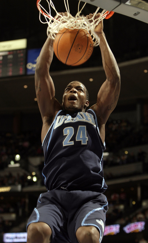 Utah Jazz rookie forward Paul Millsap hangs from the rim after dunking the ball for a basket in the fourth quarter of Utah's 96-84 victory over the Denver Nuggets in an NBA basketball game in Denver on Saturday, Jan. 6, 2007.  (AP Photo/David Zalubowski)