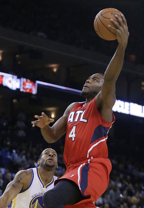 Atlanta Hawks' Paul Millsap (4) shoots over Golden State Warriors' Andre Iguodala during the first half of an NBA basketball game Friday, March 7, 2014, in Oakland, Calif. (AP Photo/Ben Margot)