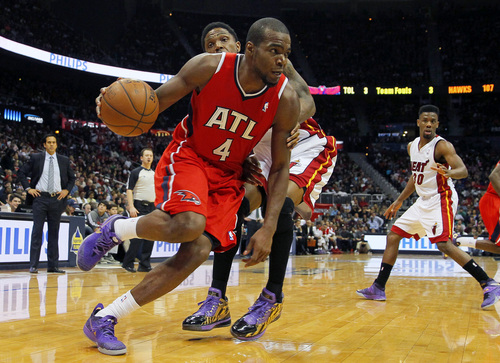 Atlanta Hawks' Paul Millsap (4) drives to the basket in front of Miami Heat power forward Udonis Haslem (40) in the third period of an NBA basketball game in Atlanta, Monday, Jan. 20, 2014. (AP Photo/Todd Kirkland)