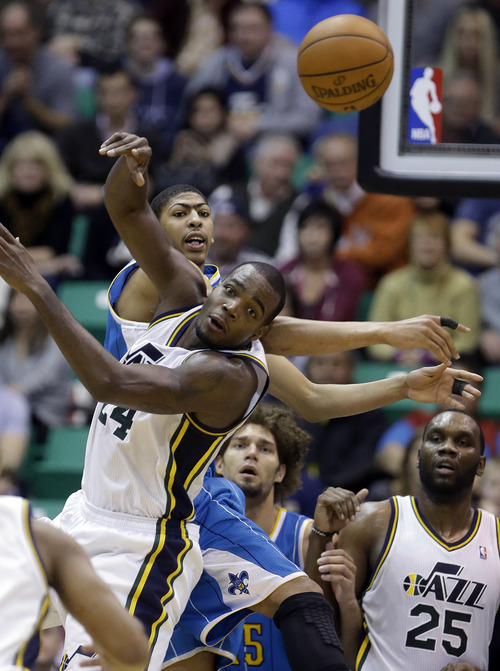 New Orleans Hornets' Anthony Davis, left, and Utah Jazz's Paul Millsap, front left, follow a jump ball as New Orleans Hornets' Robin Lopez, center rear and Utah Jazz's Al Jefferson (25) watches in the fourth quarter during an NBA basketball game Wednesday, Jan. 30, 2013, in Salt Lake City.  The Jazz defeated the Hornets 104-99. (AP Photo/Rick Bowmer)