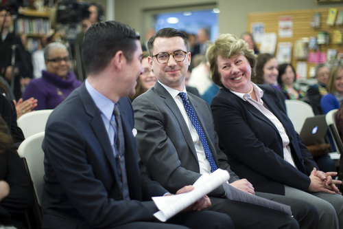 Thomas Rimbey Ogletree, center, smiles at his partner Nicholas Haddad, left, during a news conference following the announcement that a case against his father Rev. Thomas Ogletree for breaking church law by officiating their same-sex marriage had been dropped, Monday, March 10, 2014, in White Plains, N.Y. Bishop Martin McLee, who announced the decision, called on church officials to stop prosecuting other pastors for marrying same-sex couples. McLee, who leads the church's New York district said he would cease church trials over the issue in his district and would organize a broad discussion about the church's internal divisions over gay relationships.  (AP Photo/John Minchillo)