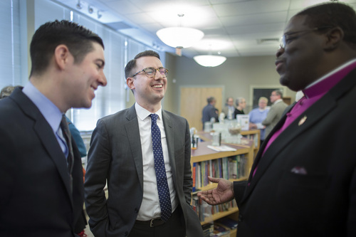 Thomas Rimbey Ogletree, center, and his partner Nicholas Haddad, left, smile during a conversation with Methodist Bishop Martin McLee following a news conference announcing the case against Ogletree's father, Rev. Thomas Ogletree, for breaking church law by officiating their same-sex marriage had been dropped, Monday, March 10, 2014, in White Plains, N.Y.   McLee, who announced the decision, called on church officials to stop prosecuting other pastors for marrying same-sex couples. McLee, who leads the church's New York district said he would cease church trials over the issue in his district and would organize a broad discussion about the church's internal divisions over gay relationships.  (AP Photo/John Minchillo)
