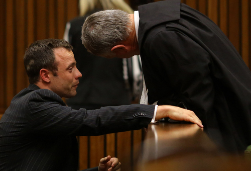 Oscar Pistorius, cries as he talks to his attorney, Barry Roux, right, after listening to evidence in cross questioning about the events surrounding the shooting death of his girlfriend Reeva Steenkamp, in court during his trial in Pretoria, South Africa, Monday, March 10, 2014. Pistorius is charged with the shooting death of his girlfriend Steenkamp, on Valentines Day in 2013. (AP Photo/Siphiwe Sibeko, Pool)