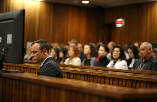Oscar Pistorius sits in the dock as he listens to cross questioning about the events surrounding the shooting death of his girlfriend Reeva Steenkamp at court during his trial in Pretoria, South Africa, Monday, March 10, 2014. Pistorius is charged with the shooting death of his girlfriend  Steenkamp, on Valentines Day in 2013. (AP Photo/Siphiwe Sibeko, Pool)