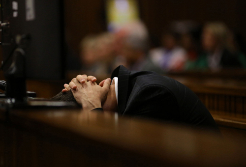 Oscar Pistorius covers his head as he listens to cross questioning about the events surrounding the shooting death of his girlfriend Reeva Steenkamp, in court during his trial in Pretoria, South Africa, Monday, March 10, 2014. Pistorius is charged with the shooting death of his girlfriend  Steenkamp in 2013. (AP Photo/Siphiwe Sibeko, Pool)