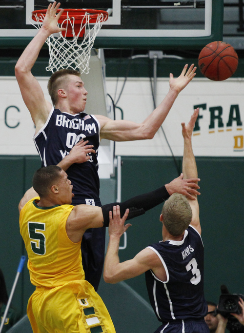 San Francisco's Matt Glover, lower left, and BYU's Eric Mika, top, and Tyler Haws reach for a rebound during the first half of an NCAA college basketball game, Thursday, Jan. 16, 2014, in San Francisco. (AP Photo/George Nikitin)