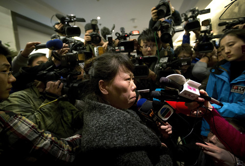 A Chinese relative of passengers aboard a missing Malaysia Airlines plane is surrounded by media as she answers questions about how families are being compensated outside a hotel room set aside for relatives or friends of passengers aboard the missing airplane in Beijing, China Tuesday, March 11, 2014.  Authorities hunting for the missing Malaysia Airlines jetliner expanded their search on land and sea Tuesday, reflecting the difficulties in finding traces of the Boeing 777 more than three days after it vanished with 239 people on board.   (AP Photo/Andy Wong)