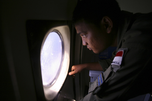 """An Indonesian Navy crew member scans the water bordering Indonesia, Malaysia and Thailand during a search operation for the missing Malaysian Airlines Boeing 777 near the Malacca straits on Monday, March 10, 2014. Dozens of ships and aircraft have failed to find any piece of the missing Boeing 777 jet that vanished more than two days ago above waters south of Vietnam as investigators pursued """"every angle"""" to explain its disappearance, including hijacking, Malaysia's civil aviation chief said Monday. (AP Photo/Binsar Bakkara)"""