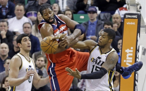 Utah Jazz's Derrick Favors, left, and Washington Wizards' Nene, center, struggle for the ball as Jazz's Enes Kanter (0) watches during the fourth quarter of an NBA basketball game Saturday, Jan. 25, 2014, in Salt Lake City. The Jazz won 104-101. (AP Photo/Rick Bowmer)