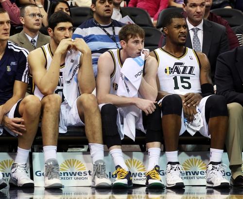 Utah Jazz's Enes Kanter, left, Utah Jazz's Gordon Hayward, middle, and Utah Jazz's Derrick Favors (15) sit on the bench late in the second half while trailing the San Antonio Spurs during an NBA basketball game on Saturday, Dec. 14, 2013, in Salt Lake City. San Antonio won the game 100-84. (AP Photo/Kim Raff)