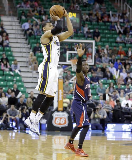 Utah Jazz's Trey Burke (3) shoots a three-pointer as Atlanta Hawks' Dennis Schroder (17) looks on in the fourth quarter during an NBA basketball game Monday, March 10, 2014, in Salt Lake City. The Hawks won 112-110. (AP Photo/Rick Bowmer)
