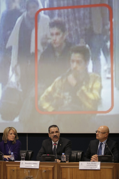 The image of two Iranian who were traveling with stolen passports on a missing  Malaysia Arlines jetliner is displayed on a screen during a presser at the Interpol headquarters in Lyon, central France, Tuesday, March 11, 2014. From left  Roraima Andriani, Interpol chief of staff, Ronald K. Noble, Secretary General of Interpol and Jean-Michel Louboutin, executive director police services.  (AP Photo/Laurent Cipriani)