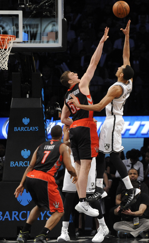 Brooklyn Nets Brooklyn Nets' Shaun Livingston (14) shoots over Toronto Raptors' Tyler Hansbrough (50) and Kyle Lowry (7) half of an NBA basketball game on Monday, March 10, 2014 at Barclays Center in New York. The Nets won 101-97. (AP Photo/Kathy Kmonicek)