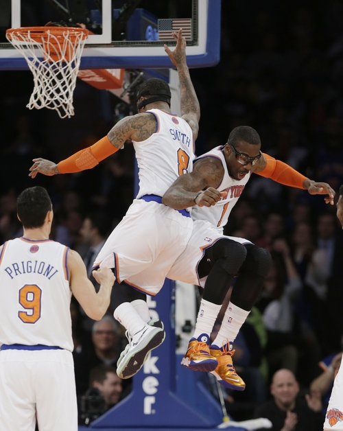 New York Knicks' Amar'e Stoudemire (1) celebrates with teammate J.R. Smith (8) as Pablo Prigioni (9) watches after Stoudemire was fouled while scoring during the second half of an NBA basketball game against the Philadelphia 76ers Monday, March 10, 2014, in New York. (AP Photo/Frank Franklin II)