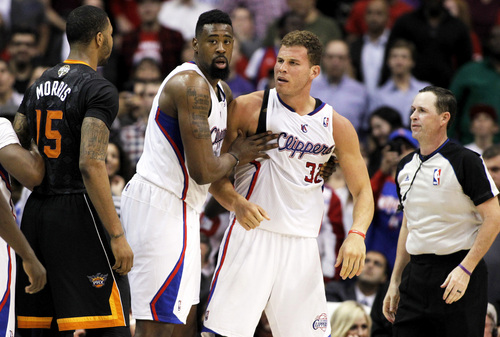 Los Angeles Clippers center DeAndre Jordan, center, pulls Clippers forward Blake Griffin (32) away from a challenge from Phoenix Suns forward Marcus Morris (15) during the second half of an NBA basketball game Monday, March 10, 2014, in Los Angeles. The Suns' PJ Tucker was ejected from the game after the play as the Clippers won 112-105.  (AP Photo/Alex Gallardo)
