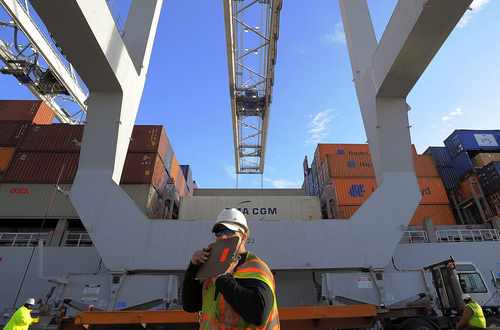In this Monday, Jan. 2, 2014, photo, a dock worker communicates on a walkie-talkie while a ship to shore crane loads containers onto a ship at the Georgia Ports Authority Garden City terminal, in Savannah, Ga. The Commerce Department releases wholesale trade inventories for January on Tuesday, March 11, 2014.  (AP Photo/Stephen B. Morton)