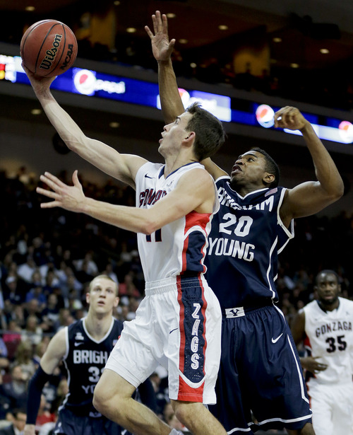 Gonzaga's David Stockton, left, puts up a shot against BYU's Anson Winder in the first half of the NCAA West Coast Conference tournament championship college basketball game, Tuesday, March 11, 2014, in Las Vegas. (AP Photo/Julie Jacobson)