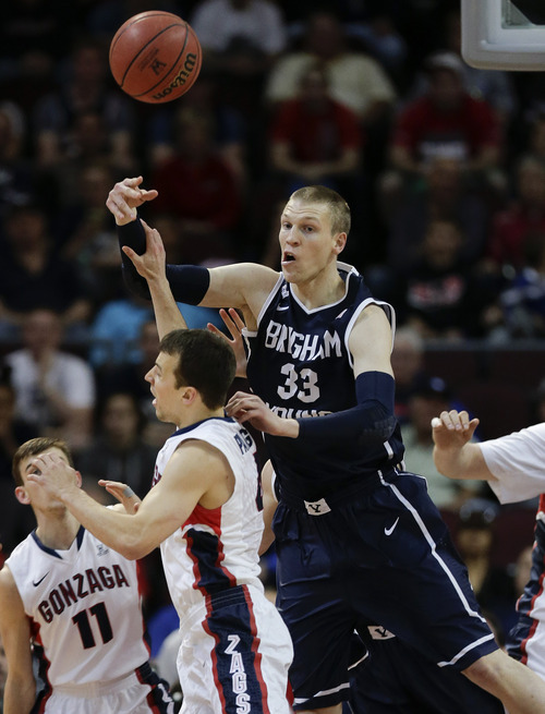 BYU's Nate Austin (33) passes the ball over Gonzaga's Kevin Pangos in the first half of the NCAA West Coast Conference tournament championship college basketball game, Tuesday, March 11, 2014, in Las Vegas. (AP Photo/Julie Jacobson)