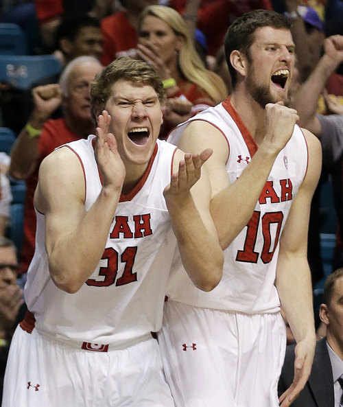 Utah's Dallin Bachynski, left, and Renan Lenz celebrate after a basket made against Washington in the second half of an NCAA Pac 12 conference tournament college basketball game, Wednesday, March 12, 2014, in Las Vegas. Utah won 67-61. (AP Photo/Julie Jacobson)