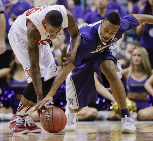 Utah's Delon Wright, left, and Washington's Darin Johnson scramble for a loose ball in the second half of an NCAA Pac 12 conference tournament college basketball game, Wednesday, March 12, 2014, in Las Vegas. Utah won 67-61. (AP Photo/Julie Jacobson)