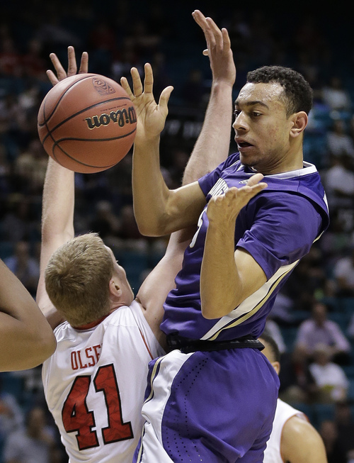 Washington's Nigel Williams-Goss, right, passes off the ball against Utah's Jeremy Olsen in the first half of an NCAA Pac 12 conference tournament college basketball game, Wednesday, March 12, 2014, in Las Vegas. (AP Photo/Julie Jacobson)