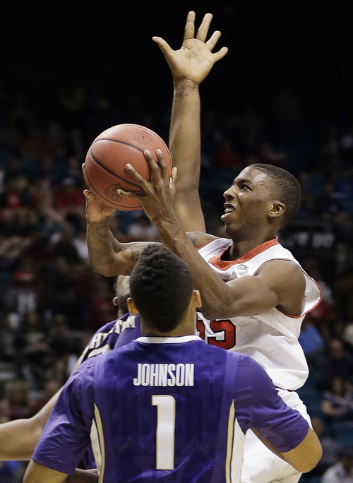 Utah's Delon Wright, right, puts up a shot against Washington's Darin Johnson in the second half of an NCAA Pac 12 conference tournament college basketball game, Wednesday, March 12, 2014, in Las Vegas. Utah won 67-61. (AP Photo/Julie Jacobson)