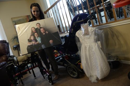 Francisco Kjolseth  |  The Salt Lake Tribune Catrina Nelson of West Jordan holds a recently made family portrait that was donated to her in honor of her youngest daughter Charlee, 6, who suffers from Late Infant Batten Disease, a terminal inherited disorder of the nervous system that leads to seizures and loss of vision and motor skills. At right is the dress they plan to bury her in when the time comes, which is expected to be soon.