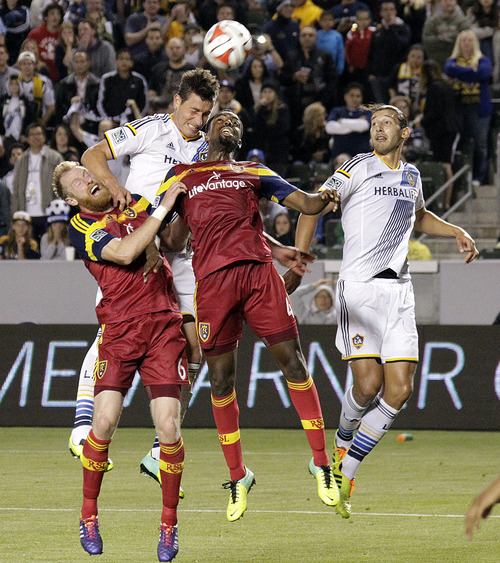 Real Salt Lake defenders Nat Borchers, left front, and Aaron Maund, collide with Los Angeles Galaxy forward Bob Friend, left rear, and defender Omar Gonzalez in the second half of an MLS soccer game in Carson, Calif., Saturday, March 8, 2014.  Real Salt Lake won, 1-0. (AP Photo/Reed Saxon)