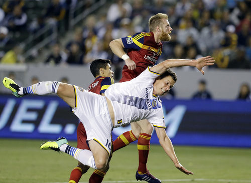 Los Angeles Galaxy forward Bob Friend, front, collides with Real Salt Lake defenders Tony Beltran, left, and Nat Borchers in the second half of an MLS soccer game in Carson, Calif., Saturday, March 8, 2014.  Real Salt Lake won, 1-0. (AP Photo/Reed Saxon)