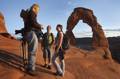 Leah Hogsten | The Salt Lake Tribune (Left to right) Photographer Dan Caldemeyer of New Mexico is asked to shoot a portrait of Taylorsville, UT residents Danny and Kelsie Johnson at sunset.  Visitors mingled around Delicate Arch to watch the sunset in the newly reopened Arches National Park , Friday, October 11, 2014.Thanks to a $1.7 million payment from Utah taxpayers, the national parks of southern Utah are being exempted from the federal government shutdown just in time for a traditionally busy fall weekend. A National Park Service report shows Utah's efforts to open nine units during the federal government shutdown paid off with visitors spending $10 for every $1 the state spent for the opening.
