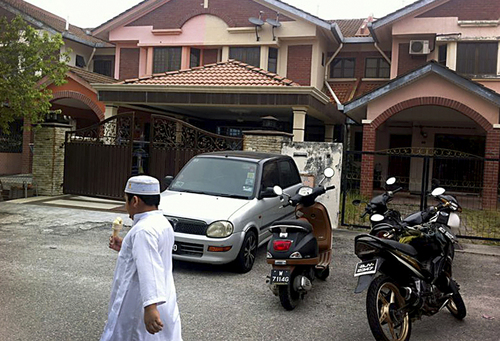 A Muslim boy leaves a mosque after Friday prayers, just down the road from the home of Fariq Abdul Hamid, co-pilot of the missing Malaysia Airlines jetliner MH370, center, Friday, March 14, 2014 in Shah Alam, Malaysia. The pilots of the missing Malaysia Airlines passenger jet were a contented middle-aged family man passionate enough about flying to build his own simulator and a 27-year-old contemplating marriage who had just graduated to the cockpit of the Boeing 777. Details about the men have emerged from interviews with neighbors, Malaysia Airlines staff, a religious leader and from social networks and news reports in Malaysia and Australia.(AP Photo/Eileen Ng)