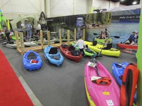 Tom Wharton  |  The Salt Lake Tribune Kids play near kayaks at the International Sportsmen's Exposition in Sandy.