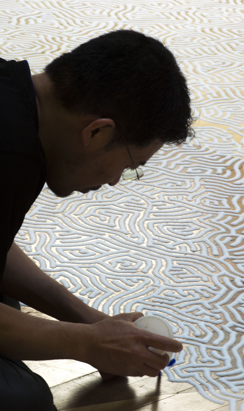 Steve Griffin  |  The Salt Lake Tribune   Artist Motoi Yamamoto works on the exhibit, Return to the Sea: Saltworks, using hundreds of pounds of Morton table salt at Westminster College  in Salt Lake City, Utah Friday, March 14, 2014.  Return to the Sea: Saltworks is open for public viewing March 10 – April 12, 2014.