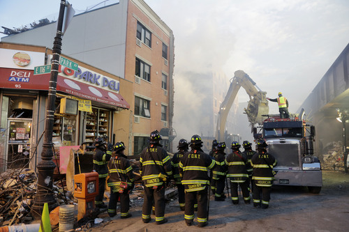 An excavator removes debris from the site of a building explosion, Thursday, March 13, 2014 in New York.  Rescuers working amid gusty winds, cold temperatures and billowing smoke pulled four additional bodies Thursday from the rubble of two New York City apartment buildings, raising the death toll to at least seven from a gas leak-triggered explosion that reduced the area to a pile of smashed bricks, splinters and mangled metal.  The explosion Wednesday morning in Manhattan's East Harlem injured more than 60 people.  (AP Photo/Mark Lennihan)
