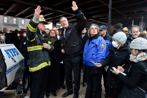 New York City Mayor Bill de Blasio, center, talks with first responders near the site of a gas leak-triggered explosion in East Harlem, Thursday, March 13, 2014, in New York. Rescuers working amid gusty winds, cold temperatures and billowing smoke pulled additional bodies Thursday from the rubble of two apartment buildings that collapsed Wednesday. (AP Photo/The Daily News, Marcus Santos, Pool)