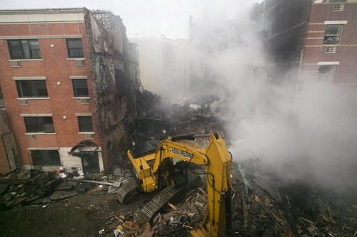 An excavator works to remove debris from  the site of a building explosion, Thursday, March 13, 2014 in New York. Rescuers working amid gusty winds, cold temperatures and billowing smoke pulled four additional bodies Thursday from the rubble of two New York City apartment buildings, raising the death toll to at least seven from a gas leak-triggered explosion that reduced the area to a pile of smashed bricks, splinters and mangled metal.  The explosion Wednesday morning in East Harlem injured more than 60 people. (AP Photo/Mark Lennihan)
