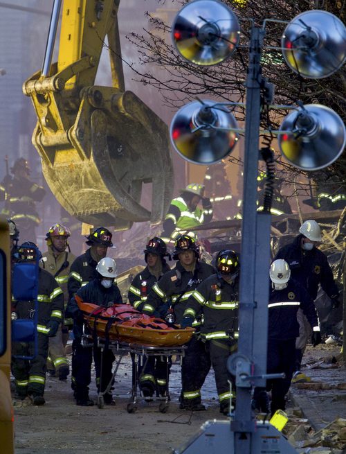 Firefighters remove a body from the scene of the gas explosion in the East Harlem neighborhood of New York,  Thursday, March 13, 2014. Rescuers working amid gusty winds, cold temperatures and billowing smoke pulled four additional bodies Thursday from the rubble of two New York City apartment buildings, raising the death toll to at least seven from a gas leak-triggered explosion that reduced the area to a pile of smashed bricks, splinters and mangled metal.  The explosion Wednesday morning injured more than 60 people. (AP Photo/Newsday, Craig Ruttle)  NYC LOCALS OUT.