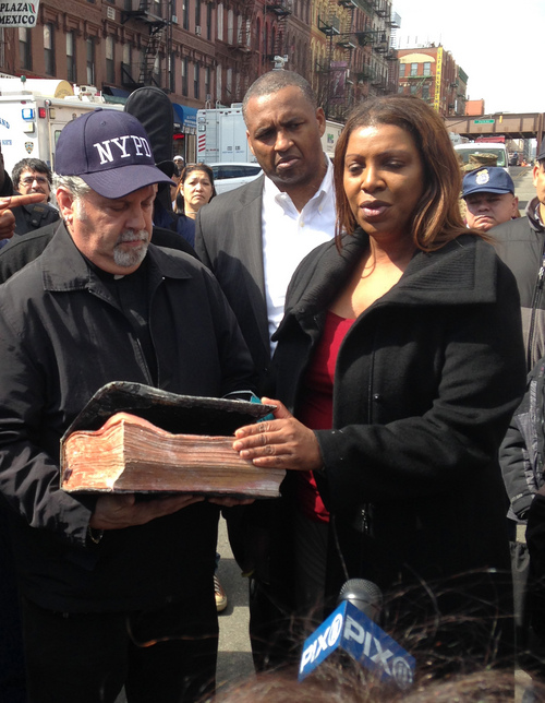 Rick Del Rio, pastor of Abounding Grace church in Manhattan, and New York City Public Advocate Letitia James, display a damaged but intact Bible they said was recovered in the rubble of the Spanish Christian Church, Saturday, March 15, 2014 in New York. The church was in one of the buildings destroyed in the March 12 gas explosion that leveled two building and killed eight people. (AP Photo/Jim Fitzgerald)