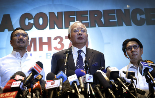 Malaysian Prime Minister Najib Razak, center, Malaysia's minister for transport Hishamuddin Hussein, left, and director general of the Malaysian Department of Civil Aviation, Azharuddin Abdul Rahman, right, delivers a statement to the media regarding missing Malaysia Airlines jetliner MH370, Saturday, March 15, 2014 in Sepang, Malaysia. Malaysian Prime Minister Najib Razak said Saturday that investigators believe the missing Malaysian airliner's communications were deliberately disabled, that it turned back from its flight to Beijing and flew for more than seven hours. (AP Photo/Wong Maye-E)