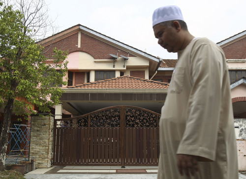 A Muslim man walks past the missing Malaysia Airlines co-pilot Fariq Abdul Hamid's house after a prayer in Shah Alam, outside Kuala Lumpur, Malaysia, Saturday, March 15, 2014. Malaysian police have already said they are looking at the psychological state, the family life and connections of pilot Zaharie, 53, and co-pilot Fariq Abdul Hamid, 27. Both have been described as respectable, community-minded men. The Malaysian jetliner missing for more than a week had its communications deliberately disabled and its last signal came about 7 1/2 hours after takeoff, meaning it could have ended up as far as Kazakhstan or into the southern reaches of the Indian Ocean, Malaysian Prime Minister Najib Razak said Saturday. (AP Photo/Lai Seng Sin)