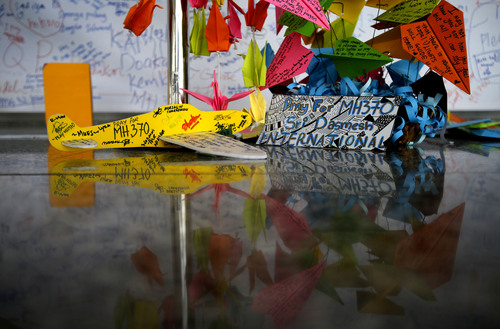 A foam plane with messages and other cards with personalized messages dedicated to people involved with the missing Malaysia Airlines jetliner MH370, is placed at the viewing gallery at Kuala Lumpur International Airport, Saturday, March 15, 2014 in Sepang, Malaysia. The Malaysian passenger jet missing for more than a week had its communications deliberately disabled and its last signal came about seven and a half hours after takeoff, meaning it could have ended up as far as Kazakhstan or deep in the southern Indian Ocean, Malaysian Prime Minister Najib Razak said Saturday. (AP Photo/Wong Maye-E)