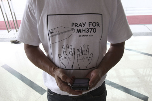 "A man wearing a T-shirt printing with ""Pray for MH370"" stands with a smartphone at a hotel in Putrajaya, Malaysia, Saturday, March 15, 2014. The Malaysian jetliner missing for more than a week had its communications deliberately disabled and its last signal came about 7 1/2 hours after takeoff, meaning it could have ended up as far as Kazakhstan or into the southern reaches of the Indian Ocean, Malaysian Prime Minister Najib Razak said Saturday. (AP Photo/Lai Seng Sin)"